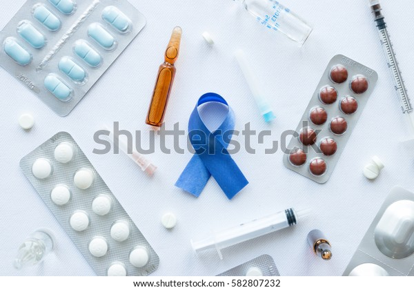 blue ribbon symbol of prostate cancer and a variety of medicines on a white background