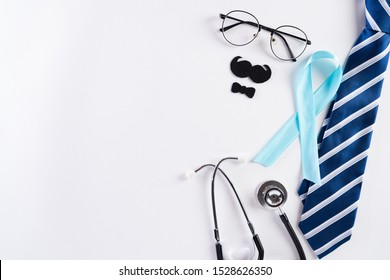 Blue ribbon with tie and stethoscope on white background representing an annual event during the month of November to raise awareness of men's health issues and prostate cancer with copy space.