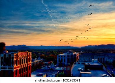 The Blue Ridge Mountains add drama to the skyline of Asheville, North Carolina at sunset.