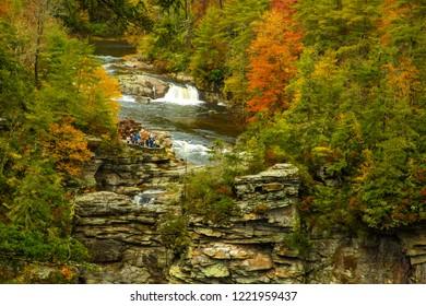 Blue Ridge Parkway, North Carolina - 10/27/2018: Hikers looking at upper Linville falls and hardfwood trees showing fall color, just off the Blue Ridge Parkway, North Carolina.