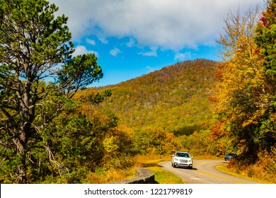 The Blue Ridge Parkway winds through a hardwood forest showing fall colorrs, North Carolina