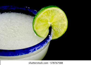Blue rimmed margarita glass with lime on a black background