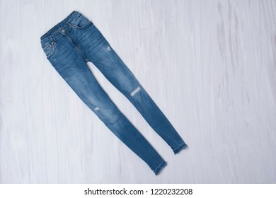 Blue ripped jeans on wooden background. Fashionable concept