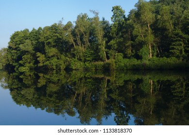 Blue river and blue sky with a lot of reflexion in the water from the surrounding trees
