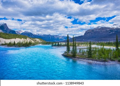 Blue river is streaming near an island with trees. A typical beautiful scenery of the rockies.