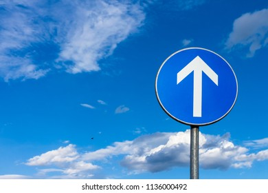 Blue road sign with with arrow pointing up at the blue sky with some white clouds