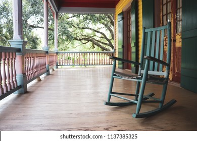 Blue rocking chair sitting on the porch of a yellow and turquoise walled plantation with wooden shutters