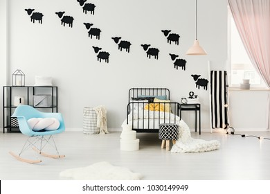Blue rocking chair and stool in cozy bedroom interior with pastel lamp above bed and black sheep stickers on the wall