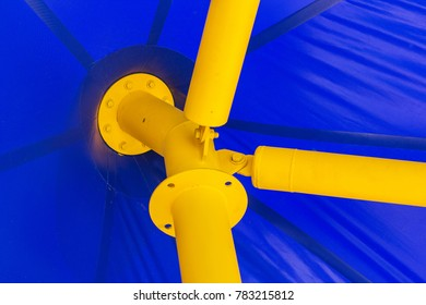Blue roof tent and yellow tent pole, close up view.