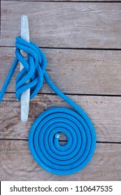 Blue rope coiled on a wooden dock and tied to a metal cleat.