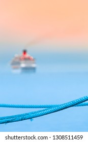 Blue rope harbor detail, departed cruise ship at blurred background (copy space)