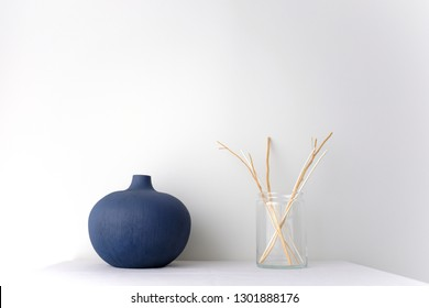 Blue round ceramic China vase and glass vase with wicker rattan reed on white table top on white background in natural light with copy space Minimal Asian interior styling.