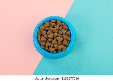 Blue round feeding bowl with dark brown heart shaped pet kibble on a blue and pink background