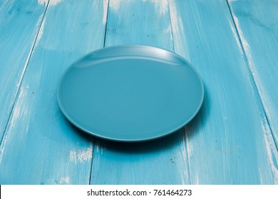 Blue Round plate on blue wooden table with perspective side view