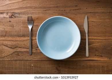 Blue Round Plate with utensils on brown wooden table background