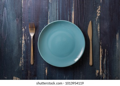 Blue Round Plate with utensils on ocean blue wooden table background