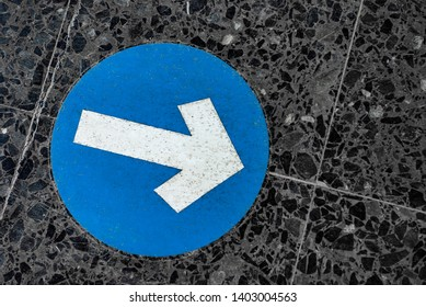 Blue round traffic road sign with white arrow symbol pointing right