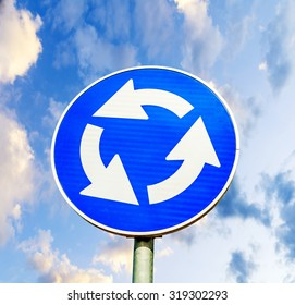Blue roundabout crossroad road traffic sign against blue cloudy sky