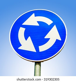 Blue roundabout crossroad road traffic sign against blue background