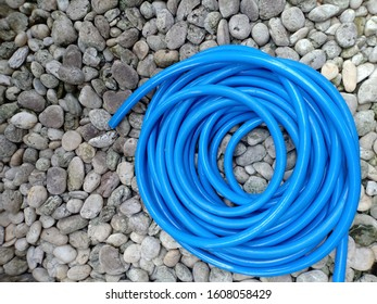 Blue rubber hose for watering plants on the stone surface.