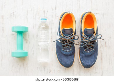 Blue running shoes with fitness accessories on white wooden background, Healthy concept
