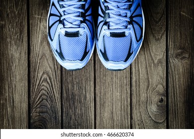 Blue running shoes on wooden background Top View