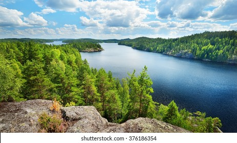 Blue Saimaa lake, rocks, evergreen trees, Finland, aerial view. Picturesque panoramic scenery. Atmospheric landscape. Pure nature, ecology, environmental conservation, ecotourism, travel destinations