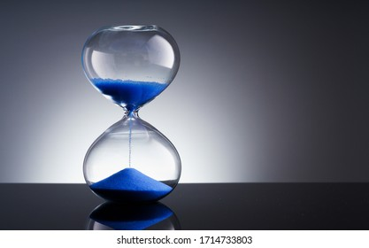 Blue sand hourglass on black background