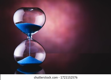 Blue sand hourglass on old background