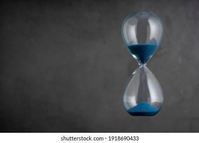 Blue sand hourglass on vintage background
