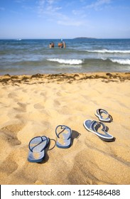 Blue sandal flip flop on a sand beach and group of happy playing people in the distance in the water