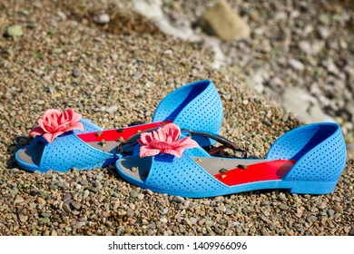 blue sandals on the beach by the sea, summer vacation concept.