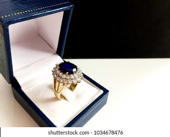 Blue sapphire egg shape ring surrounded by diamond in blue jewel box on black and white background.