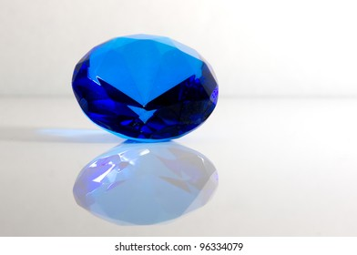Blue Sapphire Isolated on White Background with Reflection
