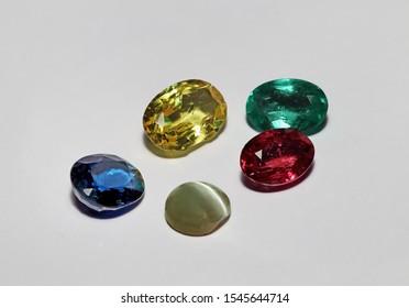 A blue Sapphire, yellow sapphire, Burmese ruby, Colombian emerald and cats-eye chrysoberyl gemstones.