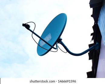 Blue satellite TV dish: Blue digital TV receiver installed next to the wall of the house or building. On the background of the blue sky with white clouds With copy space