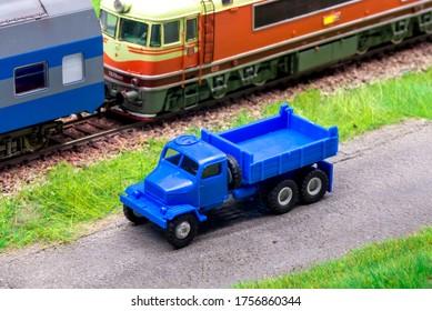 Blue scale truck on model train railroad layout road near train