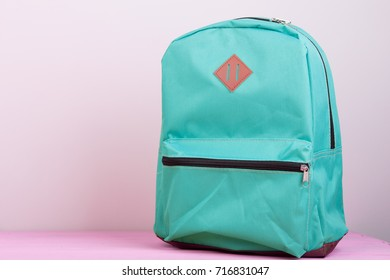 Blue school backpack is on a pink wooden table on pink background