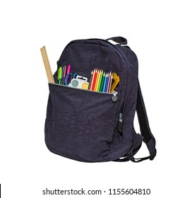 Blue school bag, backpack. Contains watercolor, ruler, color pencils, protractor, scissors. Isolated on white.