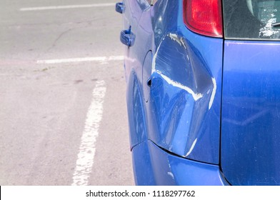 Blue scratched car with damaged paint in crash accident or parking lot and dented damage of metal body from collision