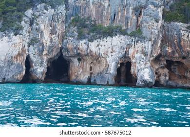 Blue sea and the characteristic caves of Cala Luna, a beach in the Golfo di Orosei, Sardinia, Italy.