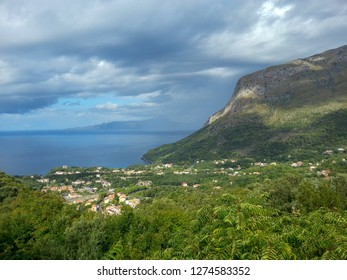 Blue and blue sea, city, rocks under the sky with clouds and fancy shadows on the mountain, Maratea, Basilicata, Potenza, Italy