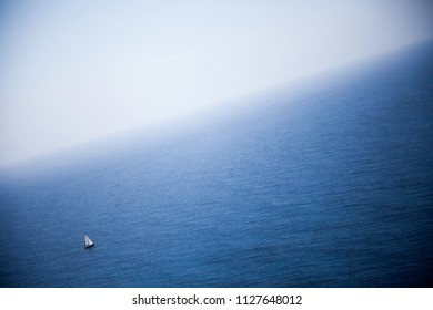 Blue sea from an elevated viewpoint with a small sailboat on a clear and sunny day