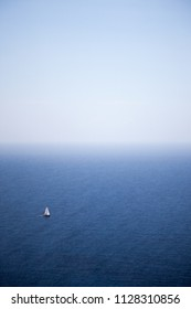 Blue sea from an elevated viewpoint with a small sailboat on a clear and sunny day from a mediterranean island
