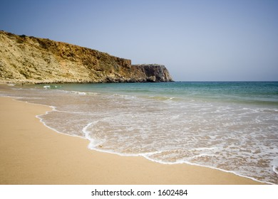 blue sea, golden sand and cliff