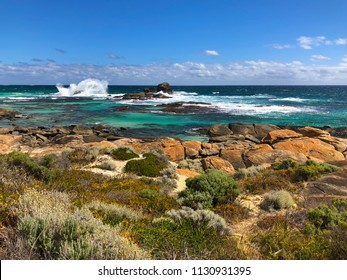 Blue sea with Granite boulders on Redgate Beach with high waves breaking, view of rock on rocky coast, Margaret River, WA, Australia