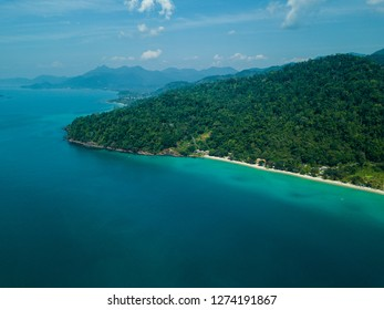 The blue sea and the green forrest are meeting at Thailand. Far away you can see big mountains on the horizon.
