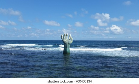 blue sea and hand shaped bronze sculpture (the hand of coexistence)