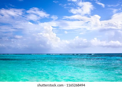 Blue sea, horizon line, blue sky with clouds background