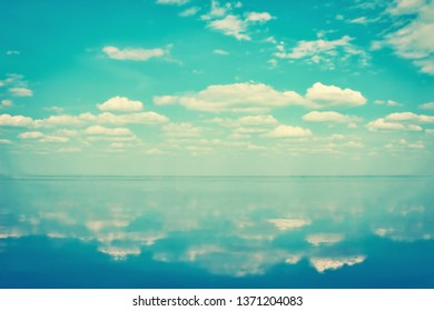 Blue sea horizon under blue sky with clouds